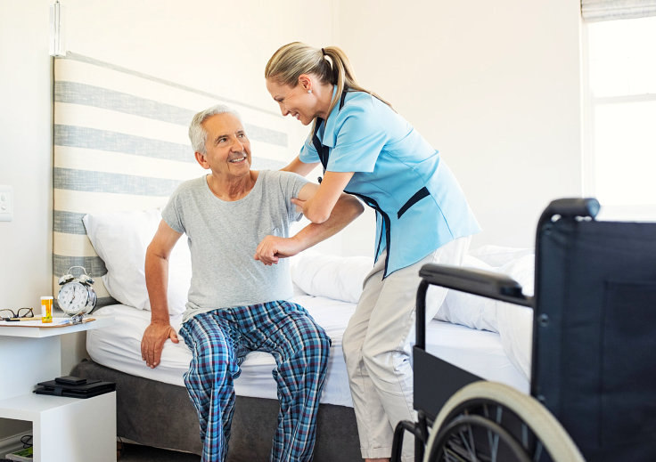 caregiver assisting senior man to stand