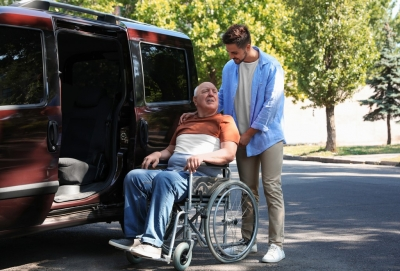 man helping his patient getting inside a van